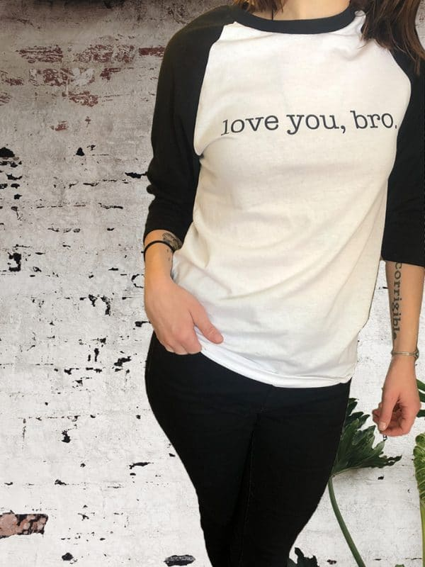 Woman wearing The Barton Brothers baseball 'love you, bro' shirt in front of a painted brick wall